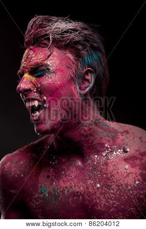 A creepy portrait of man with red body art.