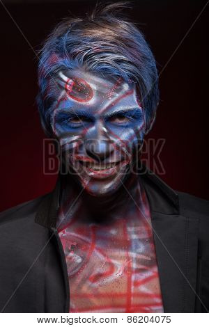 A creepy portrait of a halloween man with face art.