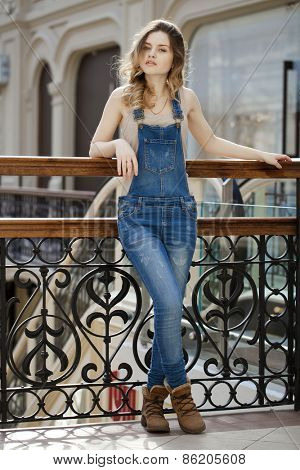 Portrait in full growth the young girl in denim overalls