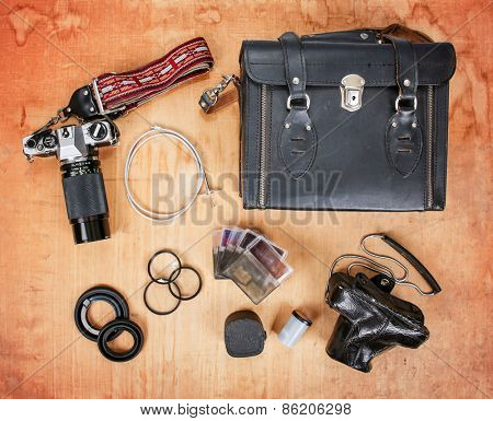 overhead image of old dirty scratched up gear needed for old school film photography enthusiasts including two cameras, a case, filters and a shutter release cable