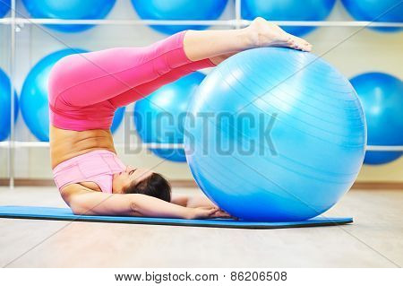 woman doing power exercises with fitness ball during pilates in sport club