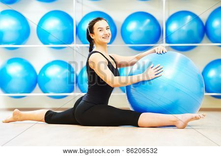 woman doing split with fitness ball during pilates stretching exercises in sport club
