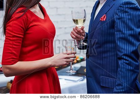Party. Two guests of formal evening party celebration holding glasses of wine in their hands