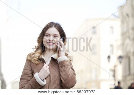 Beautiful young blonde in a fur jacket calling by phone