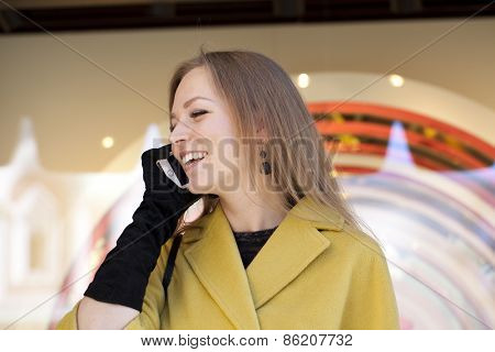 Happy beautiful girl calling by phone in yellow coat