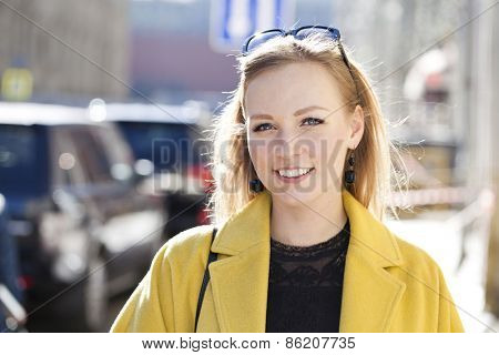 Portrait close up of young beautiful blonde woman, on spring street background