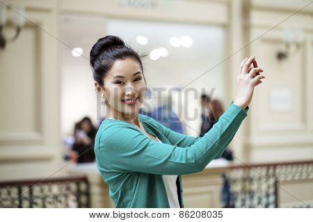 Young beautiful asian woman tourist taking pictures on mobile phone in Moscow Shop