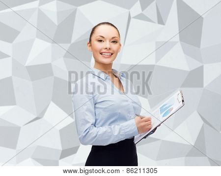 business and education concept - friendly young smiling businesswoman with clipboard and pen over gray graphic low poly background
