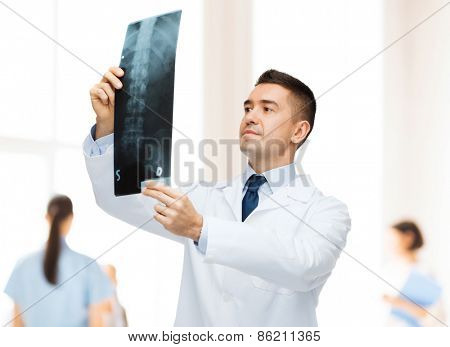 healthcare, roentgen, people and medicine concept - male doctor in white coat looking at x-ray over group of medics at hospital background
