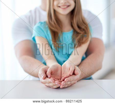 people, charity, family and advertisement concept - close up of father and girl holding something in empty cupped hands at home