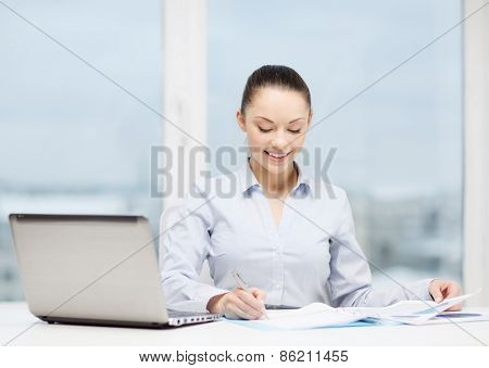 business, technology, internet and office concept - smiling businesswoman with laptop and charts in office