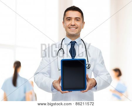 medicine, profession, advertisement and healthcare concept - smiling male doctor showing tablet pc computer blank screen over group of medics at hospital background