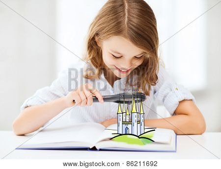 people, childhood, literature and imagination concept - little girl with book looking to fairy castle through magnifier at home
