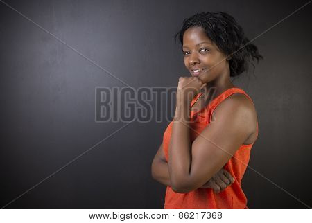 South African Or African American Woman Teacher On Chalk Black Board Background
