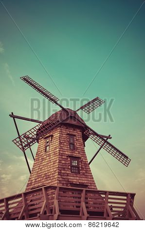 Windmill standing in the blue sky creating a nice aerial view in retro color