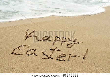 the sentence happy easter written in the wet sand of the seashore of a beach with a foamy wave in the background