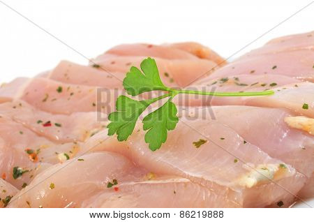 some pieces of raw chicken meat marinated with parsley and olive oil on a white background