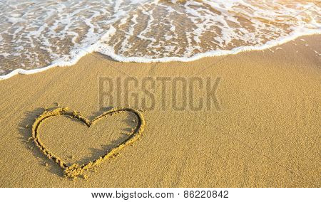 Hand drawn heart on beach sand over soft gold sunset.