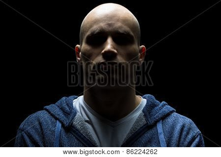 Photo of young hairless man in shadow