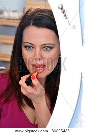 Woman applying red lipstick in dressing room mirror