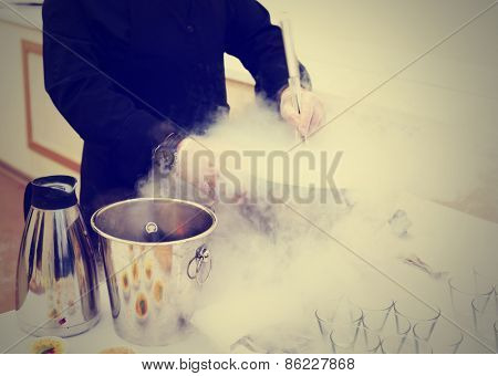 Chef is cooking ice cream with liquid nitrogen, catering event, toned image