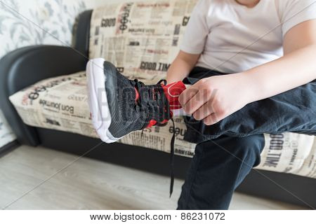 The boy wears running shoes sitting on a sofa in  room