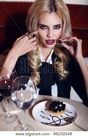 Gorgeous Woman With Blond Hair Sitting In Cafe With Wine And Dessert