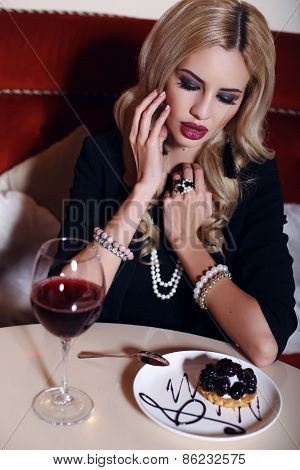 Woman With Blond Hair Sitting In Cafe With Glass Of Wine And Dessert