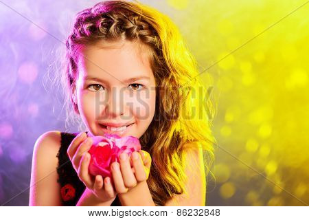 Portrait of a beautiful smiling teen girl holding rose petals in her arms. Beauty, children's fashion. Studio shot.