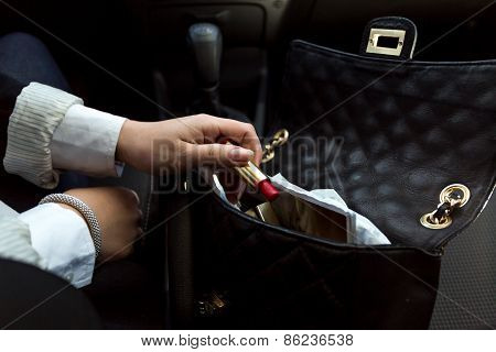 Businesswoman Taking Red Lipstick Out Of Handbag