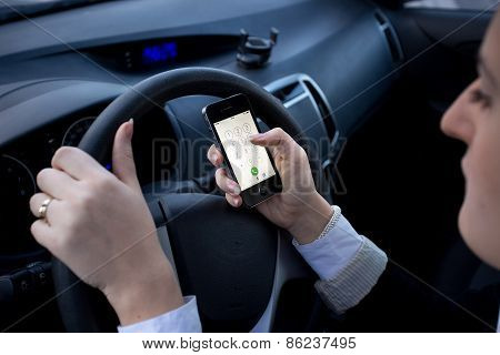Woman Entering Number On Mobile Phone While Driving A Car