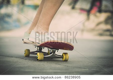 Detail of a young woman feet riding a skateboard