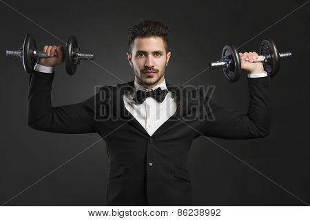 Handsome young man wearing a tuxedo a lifting weights
