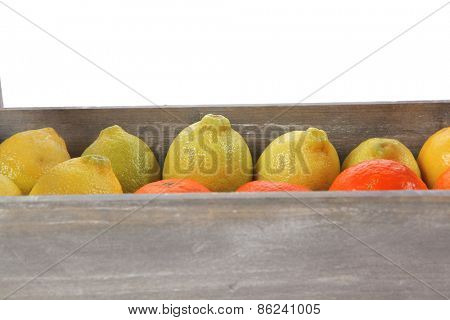 fresh raw lemon and mandarin packed in wooden box ready for transportation isolated over white background