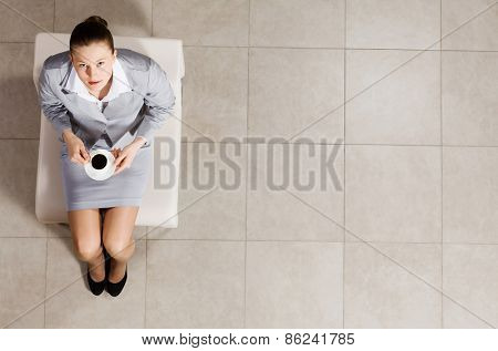 Top view of busineswoman sitting on chair with cup of coffee