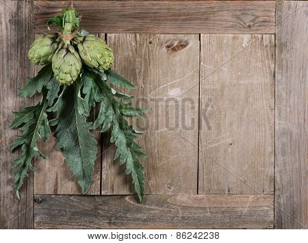 Fresh Artichokes With Leaves Hanging Over Wooden Table