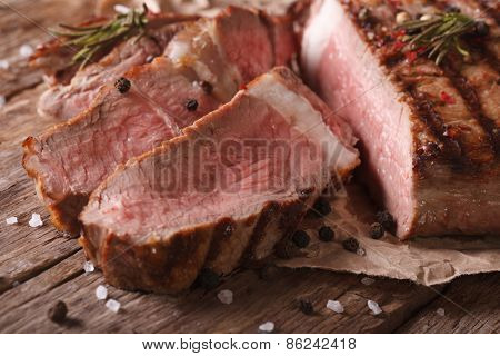 Sliced Grilled Beef Steak On An Old Table. Horizontal Close-up