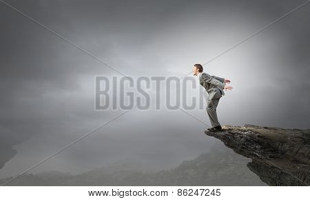 Determined businessman jumping in deep from edge of cliff