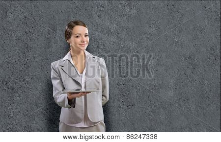 Young pretty businesswoman against grey background using tablet pc