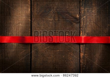 Red ribbon and rustic wooden background. Red ribbon horizontally placed on a rustic wooden surface. Intentionally shot with by-the -window like lighting and low key shadows.