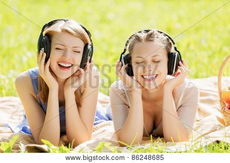 Young attractive girls in summer park wearing headphones