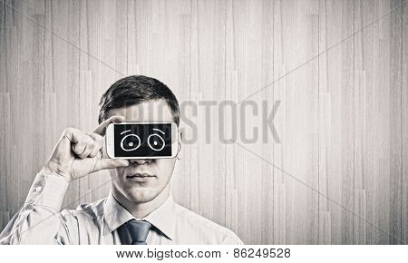 Young handsome businessman hiding mouth behind mobile phone