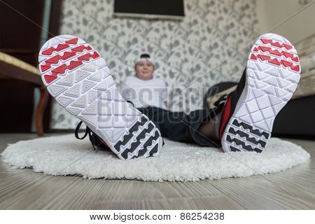 Teenager boy in running shoes at the living room