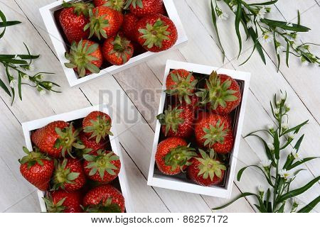 High angle image of three wood crates full of strawberries on a rustic wood surface with flowers. Horizontal format.