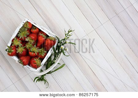 Overhead view of a basket of fresh picked strawberries on a white rustic wood table. A sprig of flowers is stuck between the handle and the basket. Horizontal format with copy space.