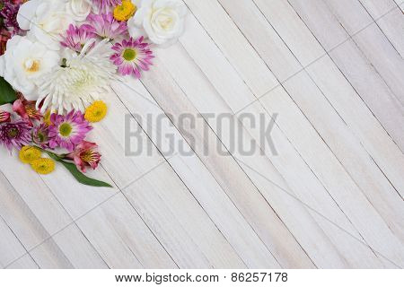High angle shot of a bunch of flowers in the upper left corner of the frame. Colorful spring time flowers on a rustic white wood table with copy space.