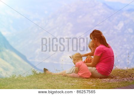 mother with kids looking on map while travel in mountains