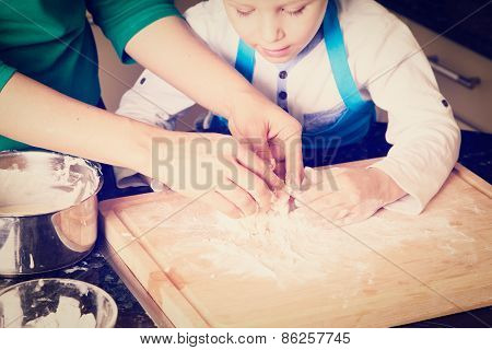hands of mother and child kneading dough