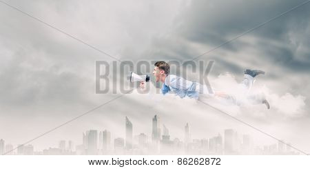 Young businessman with megaphone flying high in sky