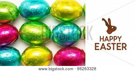 happy easter graphic against colourful foil wrapped easter eggs overhead shot